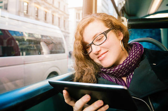 Woman sits on the bus reading a book
