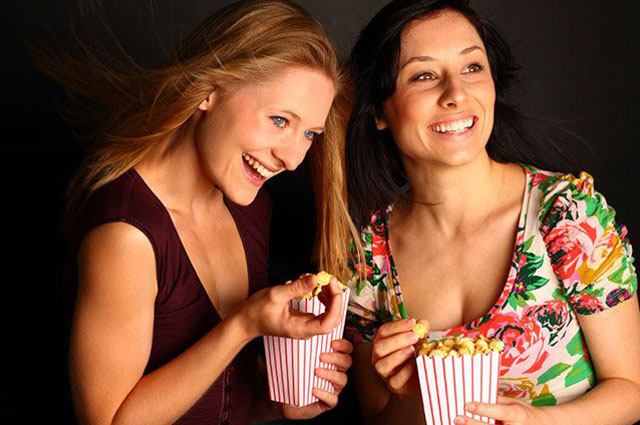 Two girls eating popcorn while watching a movie