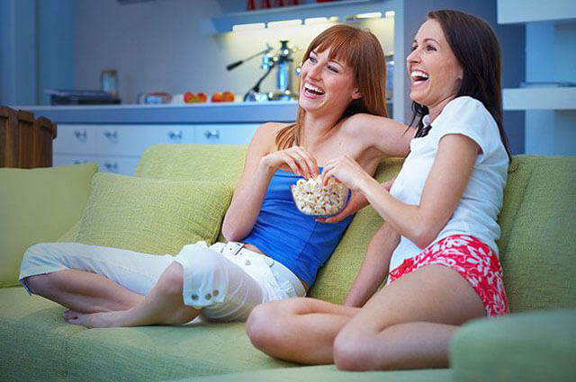 Two girls eating popcorn while watching tv
