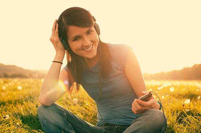 Girl sits in the field listening to music